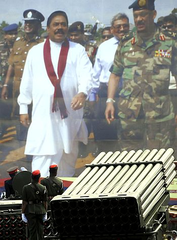 Sri Lankan army troops move past the portrait of President Mahinda Rajapakse and then Army Chief Sarath Fonseka during the National Victory Ceremony in Colombo June 3