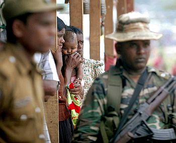 Members of the armed forces stand guard near internally displaced people (IDPs) who are living at the Ananda Kumarswami camp at Manik Farm in northern Sri Lanka
