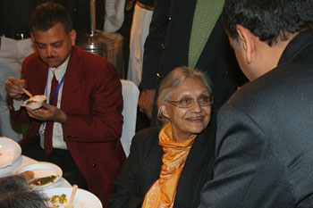 the Delhi CM interacts with a guests while having dinner