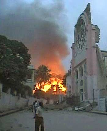 A fire breaks out near a building, which was damaged after a major earthquake struck capital Port-au-Prince