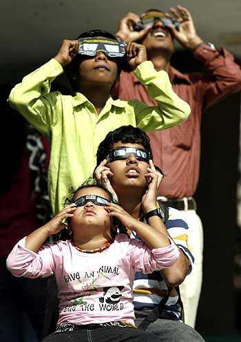 People use solar viewers to view an annular solar eclipse at the Nehru planetarium in Mumbai