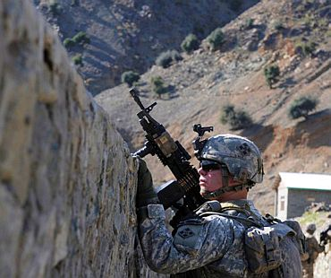 A US Army gunner peers over a canal wall during a patrol along the Kunar River in Kunar province