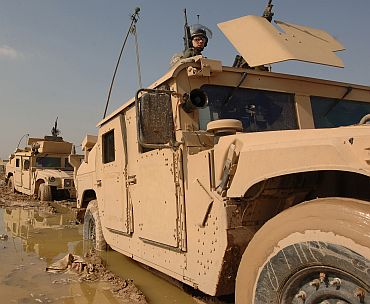 US Army soldiers maneuver their Humvees through the mud during a convoy patrol