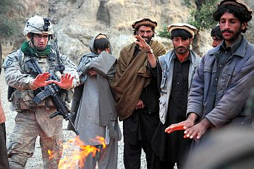 A US oldier warms his hands by a fire alongside locals in the Zanbar province of Afghanistan