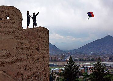 Boys fly a kite from a crumbling wall in Kabul