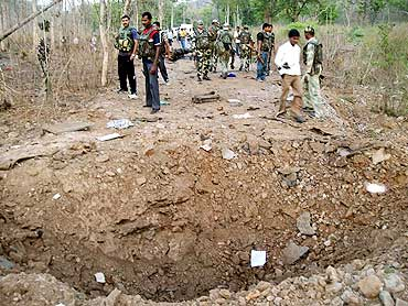 Policemen stand near a crater caused by a landmine explosion in Bijapur district, Chhattisgarh