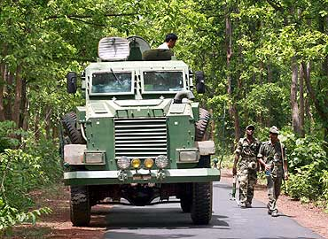 Paramilitary soldiers patrol with an anti-landmine vehicle