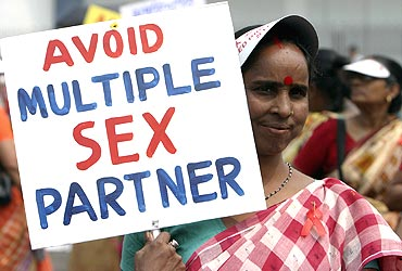 A HIV-positive woman holds a placard during an awareness rally