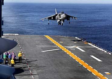 A US Marine Corps Harrier jet lands on the deck of the USS Iwo Jima