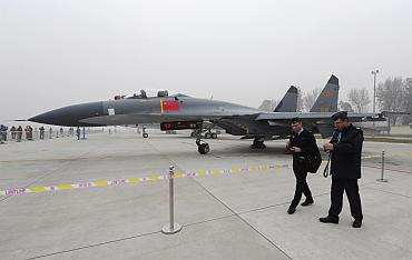 Foreign military delegates walk past a Jian-11 fighter jet on display in Beijing