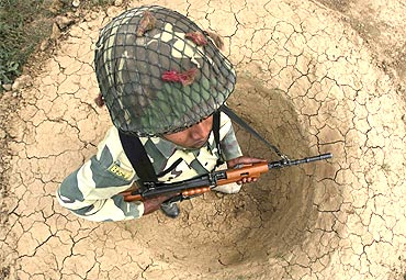 -A Border Security Force soldier stands in a trench as he guards the fenced border with Pakistan