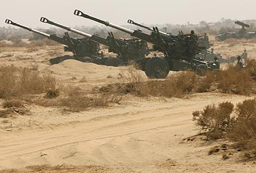 Members of Indian army's artillery take position during a joint army and air force battle exercise