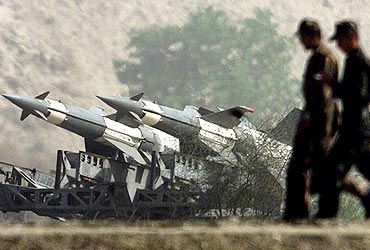Soldiers walk past missiles positioned close to the border with Pakistan