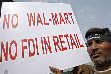 An activist from the Left parties of India holds a placard during a demonstration to protest against the entry of Wal-Mart into the Indian market, in New Delhi