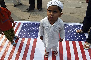 A child stands on a US flag during a protest in Lucknow