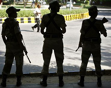 Security personnel stand guard on a road in New Delhi