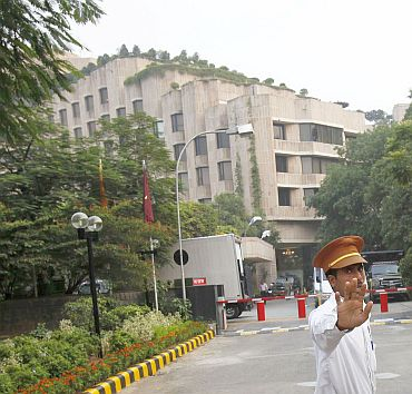 A hotel security guard stops the media outside the Hotel Maurya Sheraton