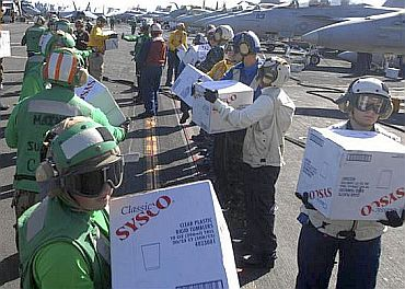 Sailors aboard the aircraft carrier USS Ronald Reagan (CVN 76) take boxes of supplies off a C-2A Greyhound from Fleet Logistics Combat Support Squadron (VRC) 30 to be transferred to the Carnival cruise ship