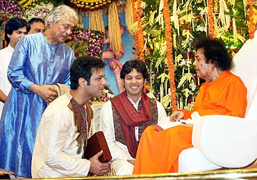 Ustad Amjad Ali Khan, sons Aayan and Amaan receiving blessings from Satya Sai Baba