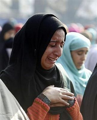 A Kashmiri woman weeps as she offers prayers during the Eid al-Adha festival in Srinagar