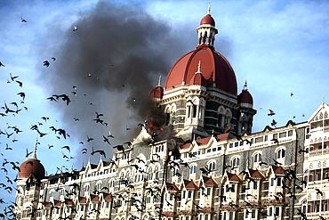 Pigeons fly near the burning Taj Mahal hotel in Mumbai during the 26/11 terror attacks