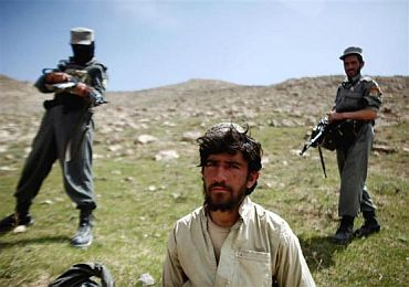 Afghan policemen stand next to a captured Taliban fighter after a gun battle near the village of Shajoy in Zabol province