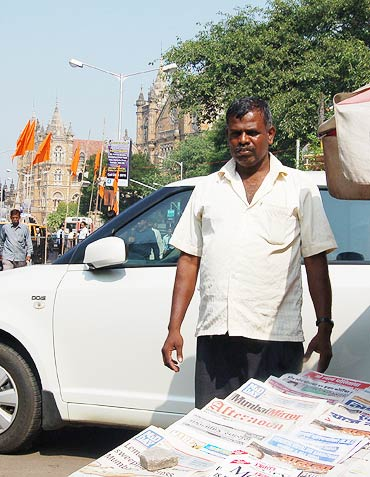 Newspaper vendor Anand Sawant outside CST (in the background)