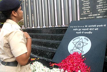 A police officers pays her respect to those who were killed in the 26/11 attacks