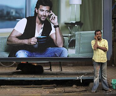 A man makes a phone call on his mobile phone in front of an advertisement for Reliance in Mumbai
