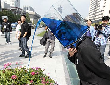 A performer wearing a transparent box with water pours water on flowers as she wanders around the street during her group's street performance 'Waterheads', as a part of the Hi Seoul Festival 2010 in central Seoul. The performance was created and performed by Australian street performance group Erth