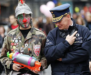 A Belgian police officer looks at a water gun carried by an activist disguised as a clown during a protest against the European Union's anti-migration policy in central Brussels on October 2