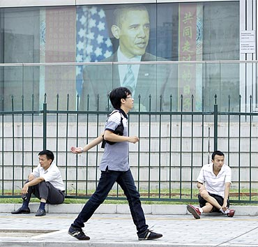 A man walks past a picture of US President Barack Obama outside the US embassy in Beijing