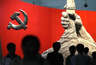 Visitors are silhouetted in front of a statue of a hand holding a gun next to a Chinese Communist Party flag at the Chinese Military Museum in Beijing