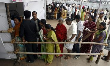 People stand in a queue to cast votes outside a polling centre in Mumbai