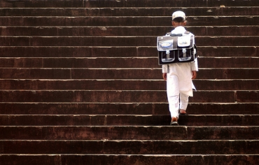 A young boy climbs the stairs of his school in Bhopal