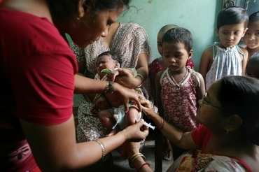 A health activist administers the Hepatitis B vaccine to a child