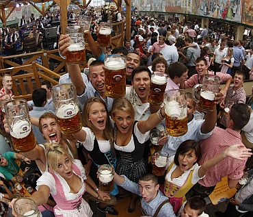 People wearing traditional Bavarian clothes toast with beer