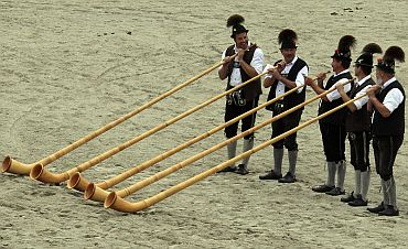 Bavarian men in traditional attire play alphorns to celebrate 200 years of Oktoberfest