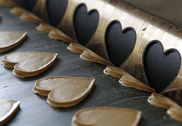 Gingerbread dough for traditional Oktoberfest hearts pass along a conveyor belt after being cut out
