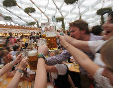 People wearing traditional Bavarian clothes toast with beer during the opening day of the 177th Oktoberfest