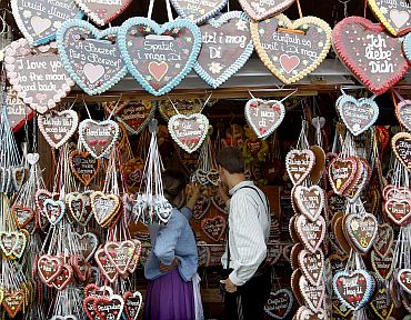 A couple look at traditional gingerbread hearts for a sale on a stall in the festival grounds
