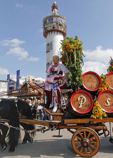 A woman in a traditional costume sits on a horse carriage during the Oktoberfest parade in Munich