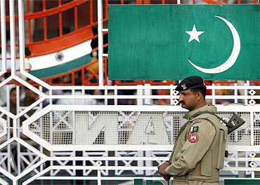 A Pakistani Ranger stands near the Pakistani flag and Indian flag during a daily parade at the check post at Wagah border