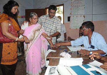 A polling officer administering indelible ink to a voter at a polling station in Thiruvananthapuram
