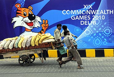 Labourers pull a hand cart loaded with bricks and sacks of sand in front of boards advertising the 2010 Commonwealth Games, over a flyover, in New Delhi