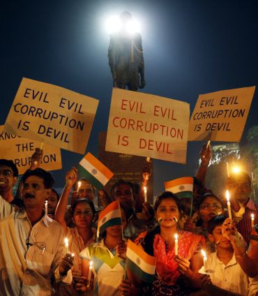 Supporters of social activist Hazare hold placards during a candlelight campaign against corruption in Ahmedabad
