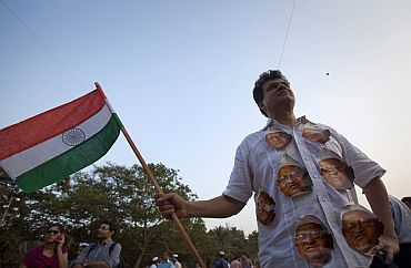 A demonstrator wearing portraits of social activist Anna Hazare on his shirt carries the national flag during a protest rally against corruption in Mumbai