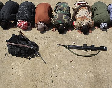 Rebel fighters pray at the front line along the western entrance of Ajdabiyah