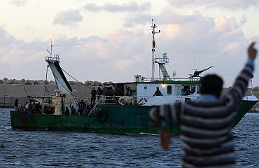 A Libyan man waves at a fishing boat carrying evacuees from Misrata at the port of Benghazi