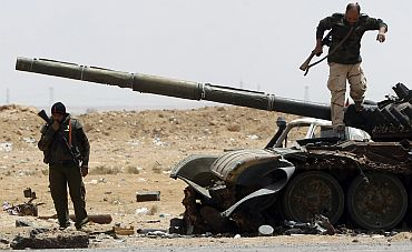 Rebel fighters walk near a destroyed tank near the front line along the western entrance gate of Ajdabiyah
